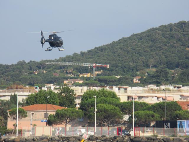 A black helicopter delivering another VIP to St. Tropez