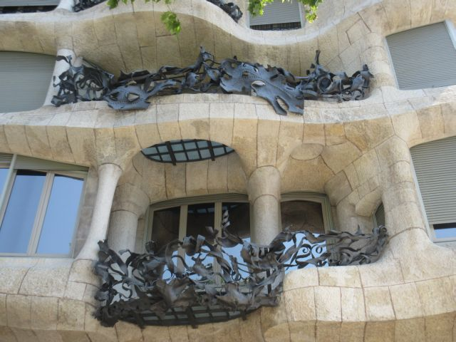 La pedrera. Built in 1905. Thestone facade and the rough iron represents the movements of the waves. Inside the building they have an exibition of his work . Even the hexagonal paving stones in this Passeig de la Gracia were designed by Gaudi.